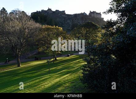 La faible lumière du soleil jette des ombres à travers les arbres dans les jardins de Princes street, avec le Château Banque D'Images