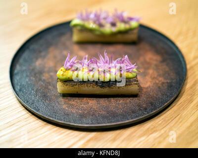 Poireau charré aux fleurs sauvages cuites par Pai Holmberg de Bifångst, un restaurant de deux places à Gothenberg. Banque D'Images