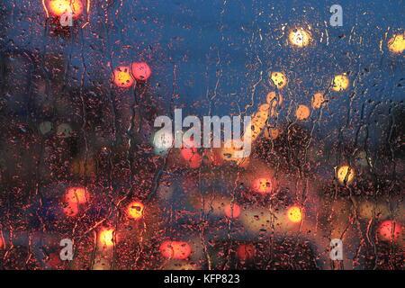Gouttes de pluie sur le pare-brise. la circulation lumière abstraite de flou artistique flou d'arrière-plan.. Banque D'Images