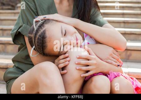 Petite fille en mettant la tête sur les genoux de la mère