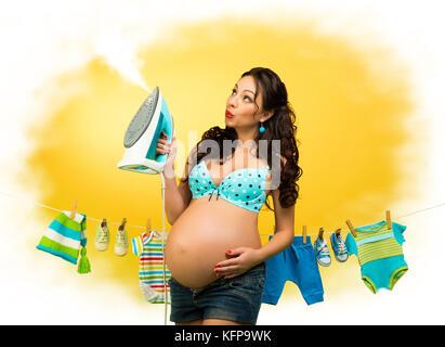 Femme enceinte avec le fer sur l'arrière-plan de vêtements pour enfants. Une broche pour attendre le bébé Banque D'Images