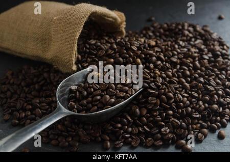 Tasse à café et grains de café torréfiés dans sac de jute sac avec feuilles sur fond de granit noir Banque D'Images