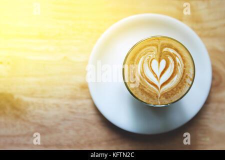 Un coeur sur latte art café sur fond de table en bois Banque D'Images