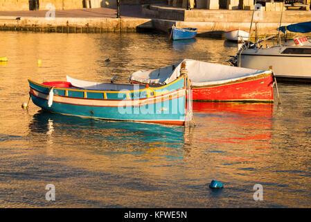 Un traditionnel, peintes de couleurs vives, ou bateau de pêche maltais luzzu amarré à Malte St Julians Bay Banque D'Images