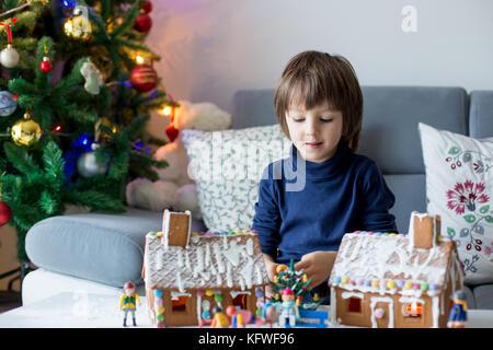 Cute child, garçon, jouer avec des maisons en pain d'épices et petits jouets à la maison à Noël Banque D'Images
