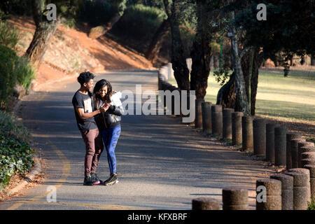 Couple un cellulaire en marchant sur une route Banque D'Images