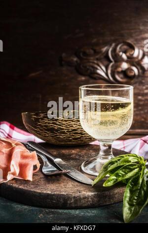 Snack traditionnel italien: jambon sec, de melon et d'un verre de vin, avec des couverts en bois foncé, fond à Banque D'Images