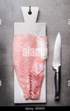 Filet de poisson cru sur en planche à découper, couteau de cuisine, fruits de mer vue d'en haut. concept Banque D'Images
