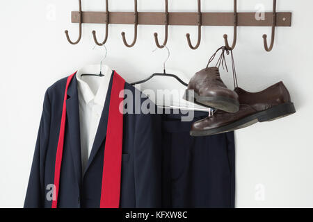 Close-up of combinaison complète et chaussures hanging on hook contre mur blanc Banque D'Images