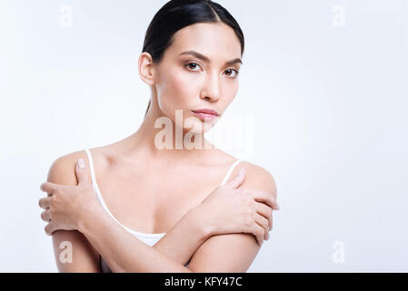 Jeune brunette posing with her arms crossed Banque D'Images