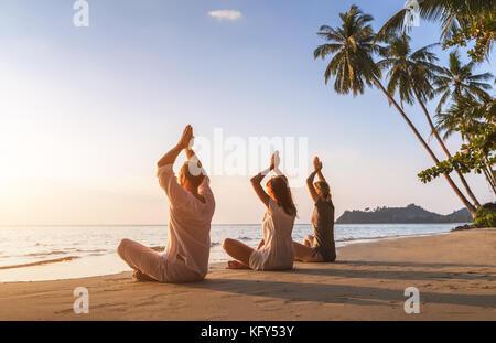 Groupe de trois personnes pratiquant le yoga lotus position sur la plage pour la détente et le bien-être, l'été Banque D'Images