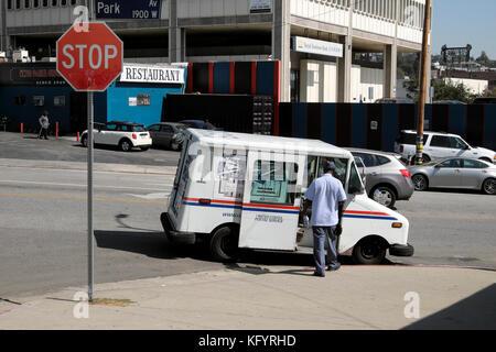 United States Postal van et mailman sur un coin de rue dans Echo Park, Los Angeles, California USA KATHY DEWITT Banque D'Images