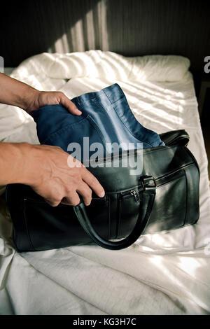 Libre d'un jeune homme de race blanche enfiler ses vêtements dans un sac de voyage ou de les mettre hors tension, Banque D'Images