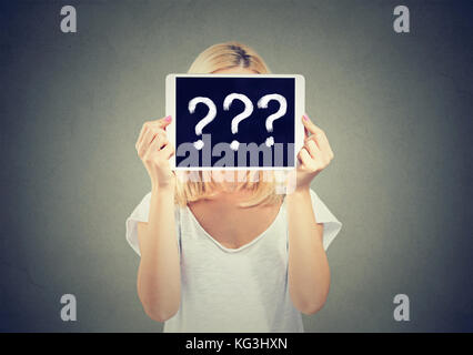 Woman holding tablet pc avec interrogation cachant son visage isolé sur fond gris. Banque D'Images