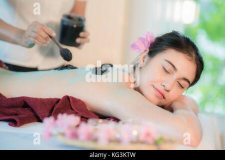 Young Asian woman receiving massage de thérapie de boue en spa salon, mettant la main sur scrub boue femelle, spa Banque D'Images