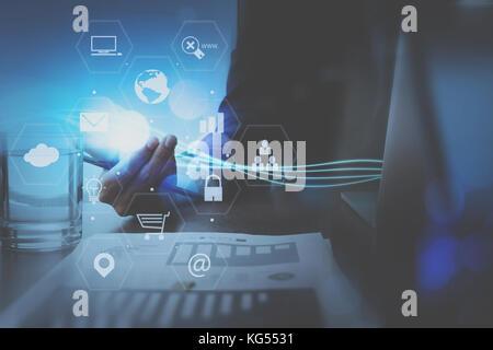 Businessman part travailler avec les ordinateurs portables ordinateur de bureau moderne en virtuel avec schéma de Banque D'Images