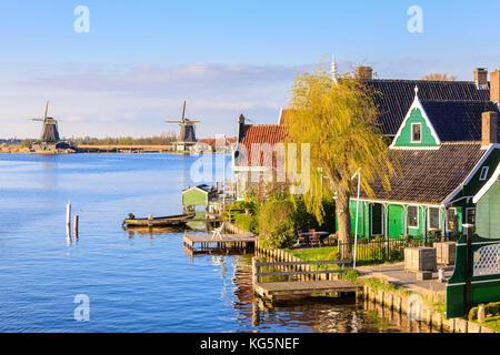Maisons en bois et le moulin se reflètent dans l'eau bleue de la rivière Zaan Zaanse Schans les Pays-Bas Hollande Banque D'Images