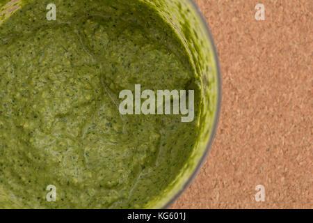 Sauce pesto vert fraîchement préparés dans un bol, gros plan arrière-plan. Banque D'Images