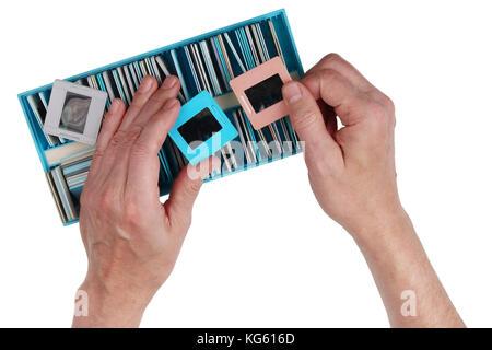 Un vieil homme regarde nostalgique à travers des diapositives couleur vieux film à partir d'une photo de famille Banque D'Images