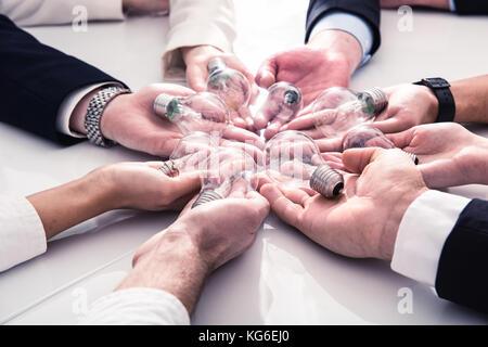 Le travail d'équipe et de remue-méninges avec les hommes d'affaires que concept partager une idée avec une lampe. Banque D'Images