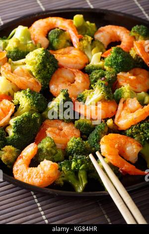 Crevettes fraîchement préparé avec brocoli close-up sur une plaque verticale. Banque D'Images
