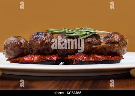 Aubergines grillées sur boulettes sauce tomate, le romarin. Un plat dans une assiette blanche, table en bois. Close Banque D'Images