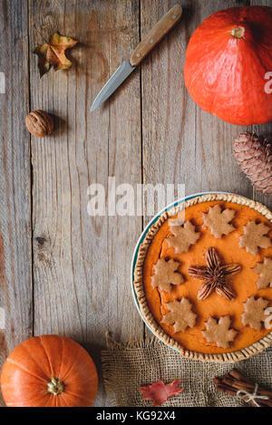 La citrouille, le potiron, le couteau et la feuille d'érable sur la vieille table en bois. L'espace de copie pour le texte. Automne confort alimentaire, jour de Thanksgiving food concept