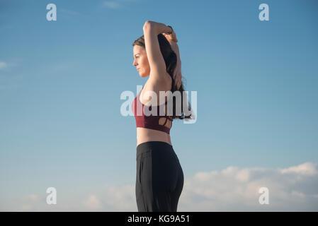 Femme sportive portant un soutien-gorge de sport faisant un bras s'étendent en dehors de garder l'ajustement. Banque D'Images