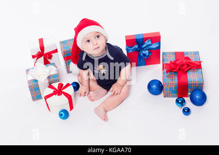 Mignon bébé assis parmi les boîtes de jouets de Noël avec des cadeaux et Banque D'Images