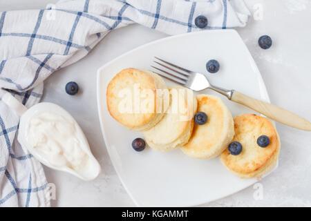 Des crêpes au fromage cottage à la crème aux fruits rouges et crème aigre. petit-déjeuner muesli sain concept. Banque D'Images