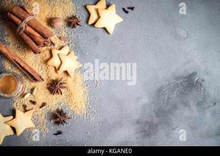 Épices de Noël, Christmas et ingrédients sur fond de béton gris. cannelle, anis étoile, muscade, cardamome, clou Banque D'Images