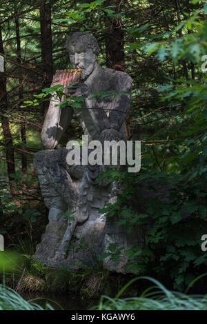 Panskulptur im Park der Iserhatsche in Bispingen auf einem Stein sitzend am Rande des Waldes mit Licht und Schatten