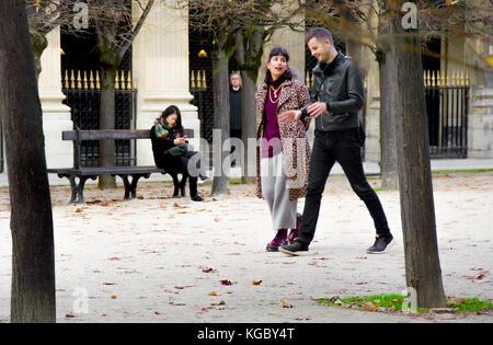 Paris, France. Palais Royal. L'automne, woman sur un banc, young couple walking passé (et un homme effrayant entre Banque D'Images