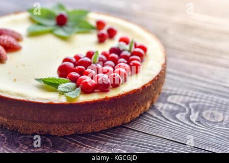 Gâteau au fromage frais aux fruits rouges sur un fond de bois. Banque D'Images