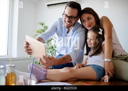 Famille heureuse de prendre dans leur maison selfies Banque D'Images