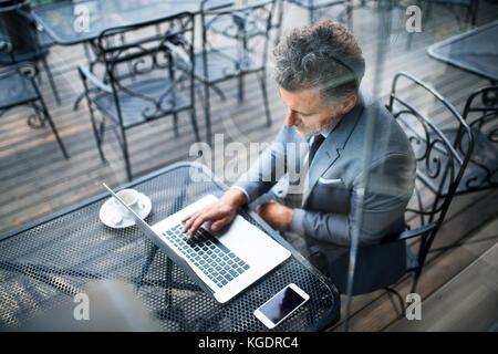 Mature businessman avec coffre à l'extérieur d'un café. Banque D'Images