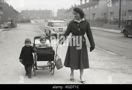 Années 1950, historiques, mère de marcher avec son jeune enfant et bébé dans la pram et près des magasins locaux Banque D'Images