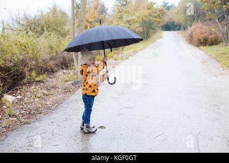 Un petit garçon marche dans la pluie automne parapluie Banque D'Images