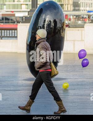 Femme marchant le long de la rive sud de Londres. Banque D'Images