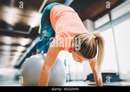 Young attractive woman doing push ups à l'aide ball Banque D'Images