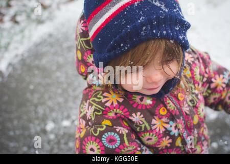 Un enfant se tient à l'extérieur portant des vêtements d'hiver avec de la neige autour d'elle.