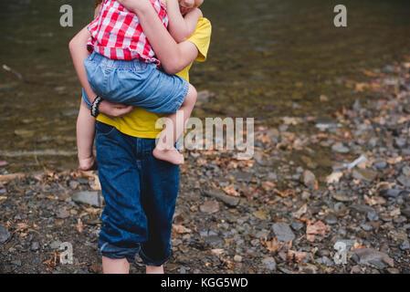 Un garçon porte un enfant dans ses bras Banque D'Images