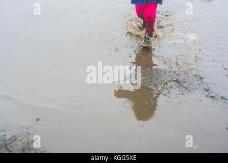 Enfant marcher dans une flaque de boue Banque D'Images