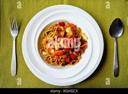 Spaghetti avec sauce aux herbes épicées Thaï et langoustines on white plate Banque D'Images