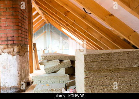 Avis de construction et rénovation grenier site avec pile de la laine prête à être installée Banque D'Images