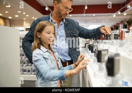 Homme avec enfant regardant dans les compacts au magasin multimédia Banque D'Images