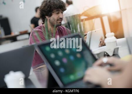 L'homme jeune entrepreneur working in office on laptop Banque D'Images