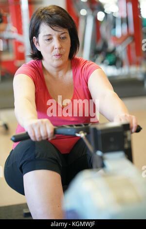 L'excès de femme dans la salle de sport faire des exercices cardio rameur sur Banque D'Images