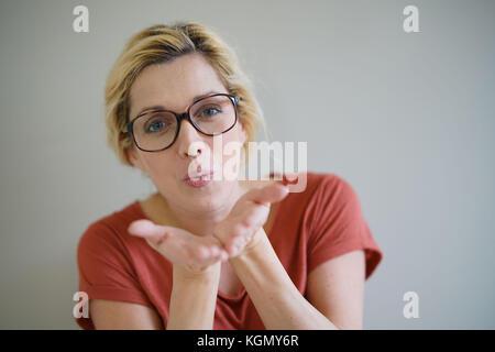 Femme blonde avec des lunettes blowing kisses vers la caméra, isolé Banque D'Images
