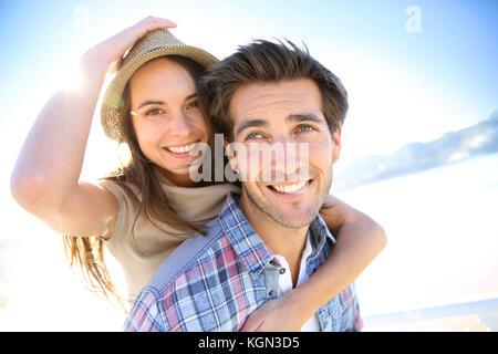 Man giving piggyback ride de petite amie à la plage